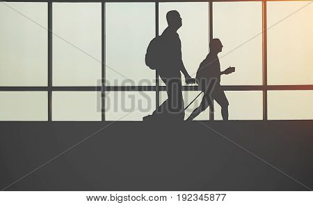 Travellers in airport walking to departures by escalator in front of window silhouette