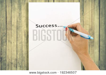 Woman's hand writing word success on white paper sheet wooden background