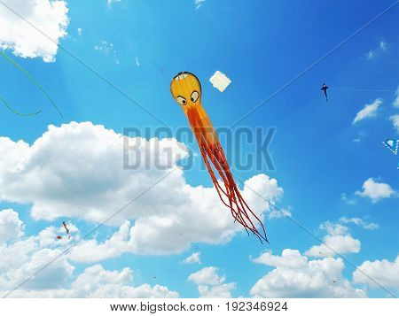 Big Kite Flying In A Blue Sky. Kites Of Various Shapes