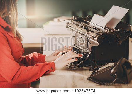 Secretary At Old Typewriter With Telephone. Young Woman Using Typewriter. Business Concepts.
