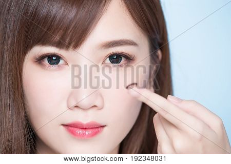 woman take contact lenses on the blue background
