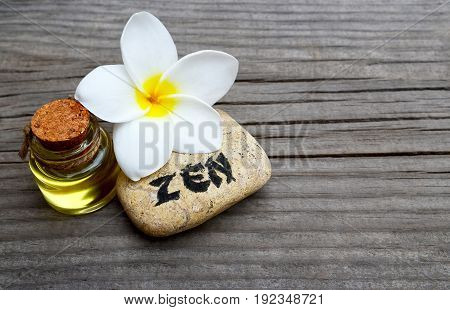 Spa decoration with massage oil,frangipani flower and zen stone on old wooden background.Spa concept.Selective focus.