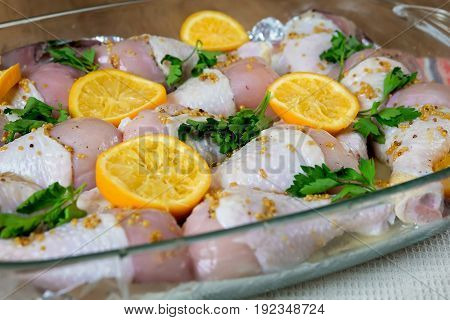 Chicken with orange, honey and mustard before baking, on a table in a baking dish.