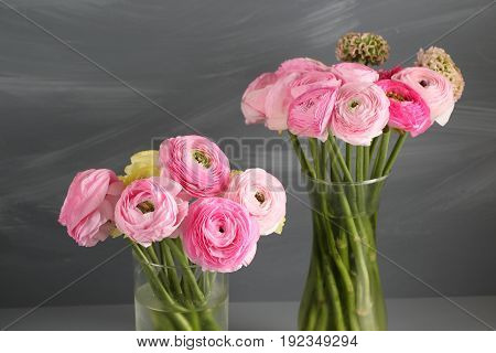 Multicolor buttercup, Ranunculus in the glass vase on the gray background