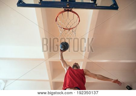 Perfect shot from above of a basketball player slam dunking.