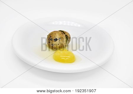 one broken quail egg on a white saucer