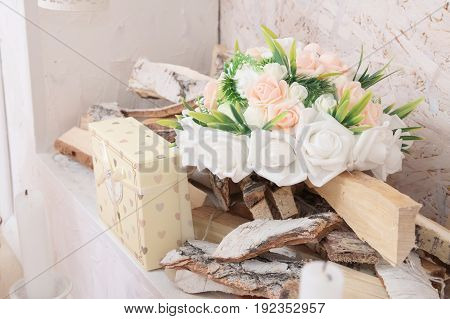 Lifestyle with white and pink flowers bouquet and girt in fireplace for lush interior. home decor. country house decor in details