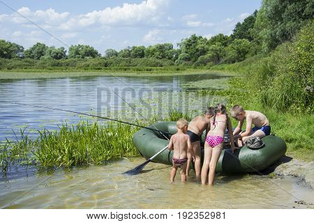 In summer on the bank of the river on a bright sunny day children gather for fishing on an inflatable boat.