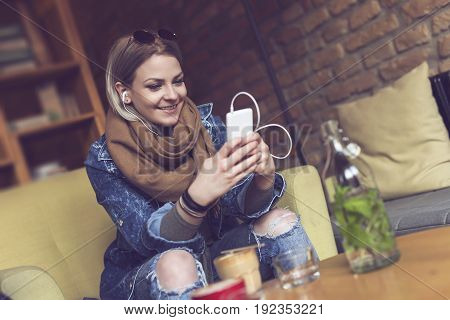 Beautiful young woman sitting in an armchair in a cafe drinking coffee and listening to the music
