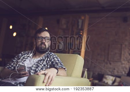 Handsome young man sitting in an armchair in a cafe and listening to the music on his smart phone