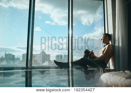 A man with a naked torso and a bottle of champagne sitting on the window