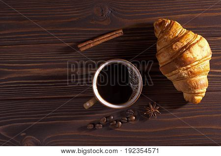 Cup of hot coffee and fresh croissant on dark wooden table top view. Low illumination. Space for text