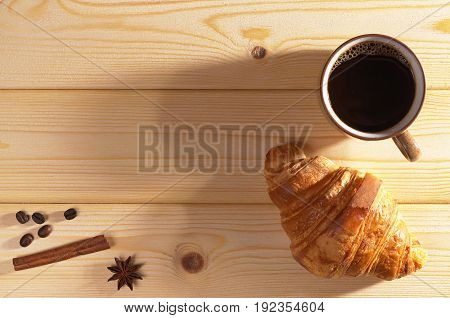 Cup of hot coffee and croissant on wooden background top view. Lower light. Space for text