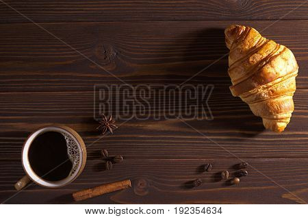 Cup of hot coffee and croissant on dark wooden background top view. Lower light. Space for text