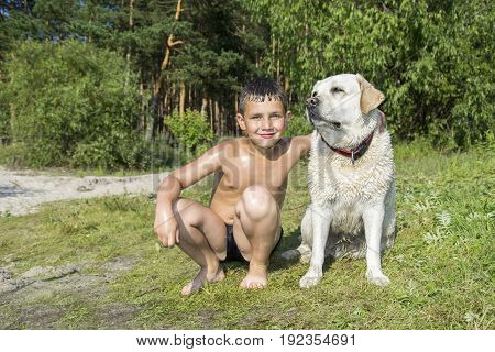 In summer a small wet boy with a large dog sits on the shore.