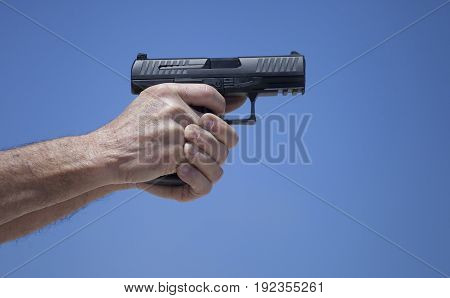 Black semi automatic handgun well gripped with sky behind