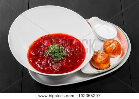Ukrainian and Russian traditional beetroot soup - borscht in plate sour cream and buns with garlic and herbs on dark wooden background. Homemade food