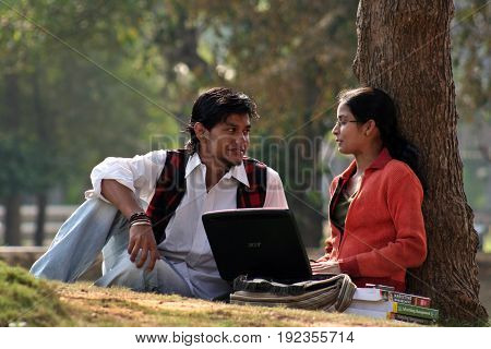 KOLKATA, DECEMBER 03, 2008: A Couple of young Indian College student is discussing with laptop and books at the campus ground on December 03, 2008 in India.