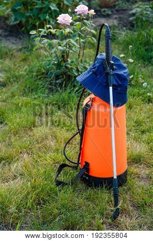 Fertilizer pesticide garden sprayer with hat on lawn with green grass