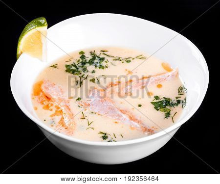 Fish soup with salmon and shrimps dill potatoes lemon and vegetables in bowl isolated on black background healthy food. Top view