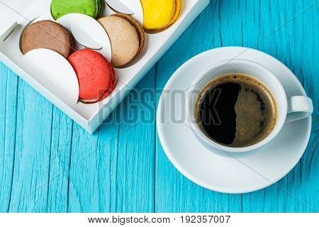 Macaroon with cup of coffee on blue table