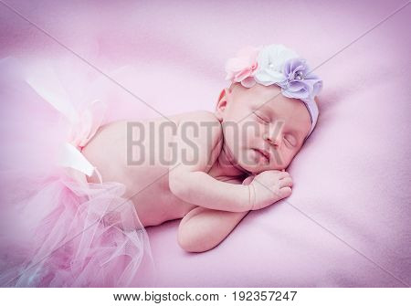 A sweet girl with a flower on her head is sleeping sweetly