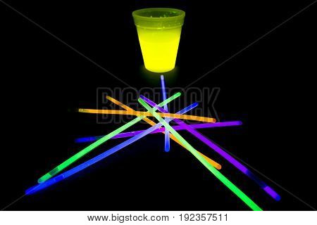Yellow fluorescent glass with glow sticks neon light on back background. variation of different colored chem lights