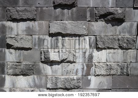 Smooth and untreated gray rectangular granite stone wall rubblework.