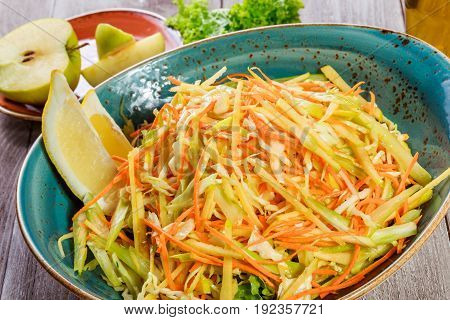 Fresh salad with apple carrot cabbage celery and lemon on wooden background close up. Healthy food. Top view