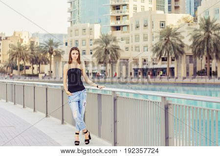 Young woman with bob cut standing near metal fence at Dubai downtown. Fashionista with brown hair standing at empty street in casual outfit