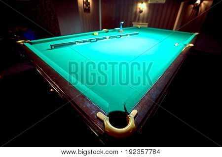 Lighted billiard table green on the service before the game.
