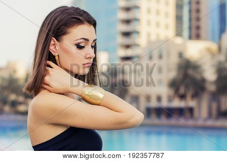 Horizontal portrait of young european female with trendy make up stylish bob cut and with golden accessories. Make up with false eyelashes