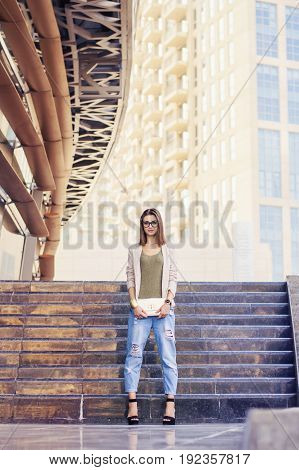 Young adult fashionista in blue boyfriend jeans jacket and high heels with small clutch and eyeglasses standing near stairs. Fashion trends concept