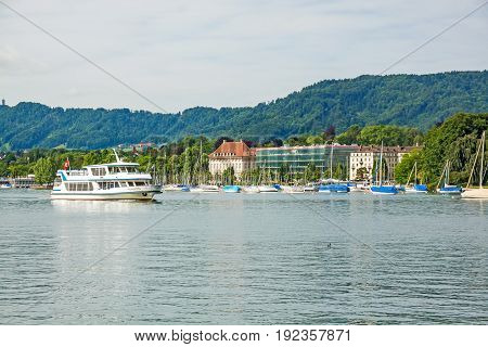 Zurich Switzerland - June 10 2017: Excursion boat arriving at shipping pier Burkliplatz. Western bank of Lake Zurich Mythenquai / Enge in background.
