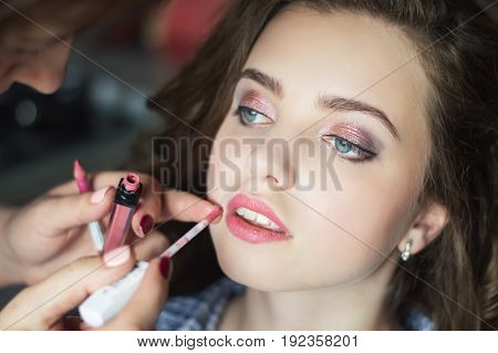 Face of a young girl of teen age with trendy make up with eye shadows and matte lipstick. Make up process. Professional make-up