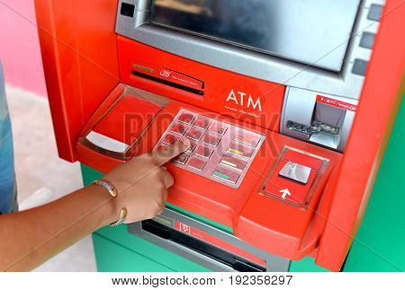 Atm machine and people finger pressing it photo in outdoor low lighing.