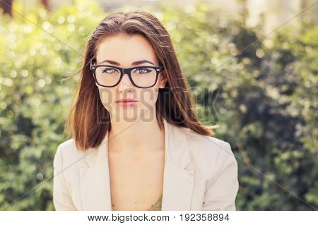Portrait of a young business woman with short hair eye glasses and beige jacket. Business look concept. Bob cut hairstyle
