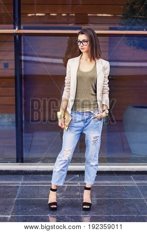 Vertical photo of a young adult female with bob cut beige jacket stylish eye glasses blue jeans golden clutch high heels standing outdoor. Casual style concept