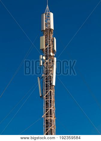 cell tower in the roof of a building against blue sky