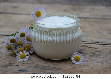 Organic cosmetic cream with chamomile flowers on a background of boards