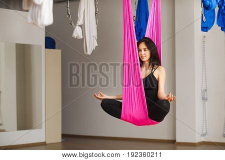 Woman sits in lotus pose in hammock and practices aerial yoga. Anti-gravity relaxing kind of sport with special clothing equipment