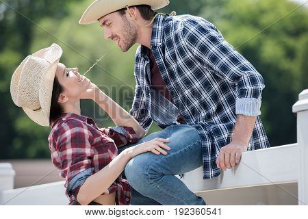 young smiling cowboy style couple flirting outdoors