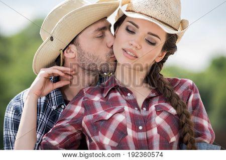 young cowboy kissing his sensual girlfriend outdoors at daytime