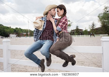 young passionate cowboy style couple kissing while sitting on fence at ranch