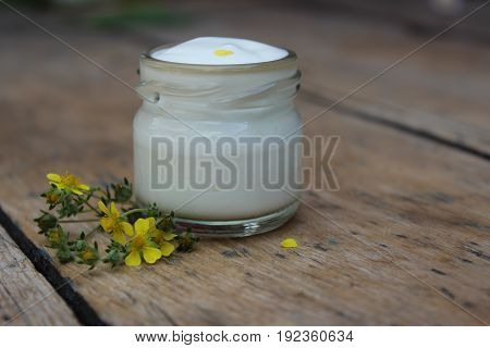 Organic cosmetic cream with yellow flowers against the background of boards