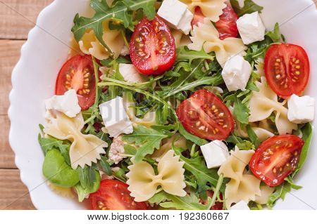 Salad with farfalle pasta feta cheese sliced cherry tomatoes baby spinach leaves arugula chicken meat in a white bowl. View from above. Healthy pasta salad