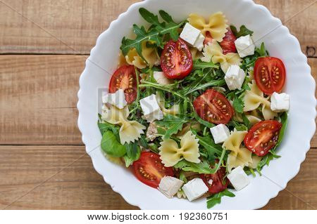 Homemade pasta salad with red cherry tomatoes feta cheese farfalle arugula baby spinach chicken meat in white salad bowl on wooden table. Healthy diet