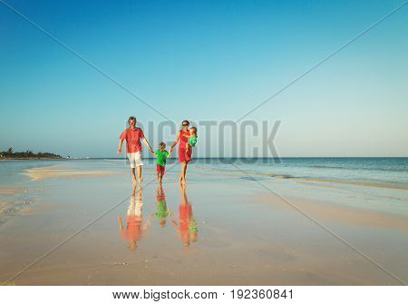 happy family with two kids run on beach, beach vacation