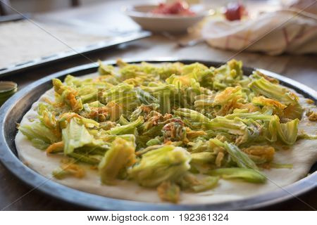 preparing pizza with zucchini flowers at home