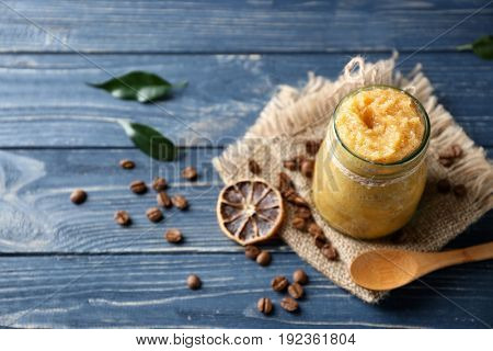 Glass jar with scrub, dried lemon slice, spoon and coffee grains on wooden background